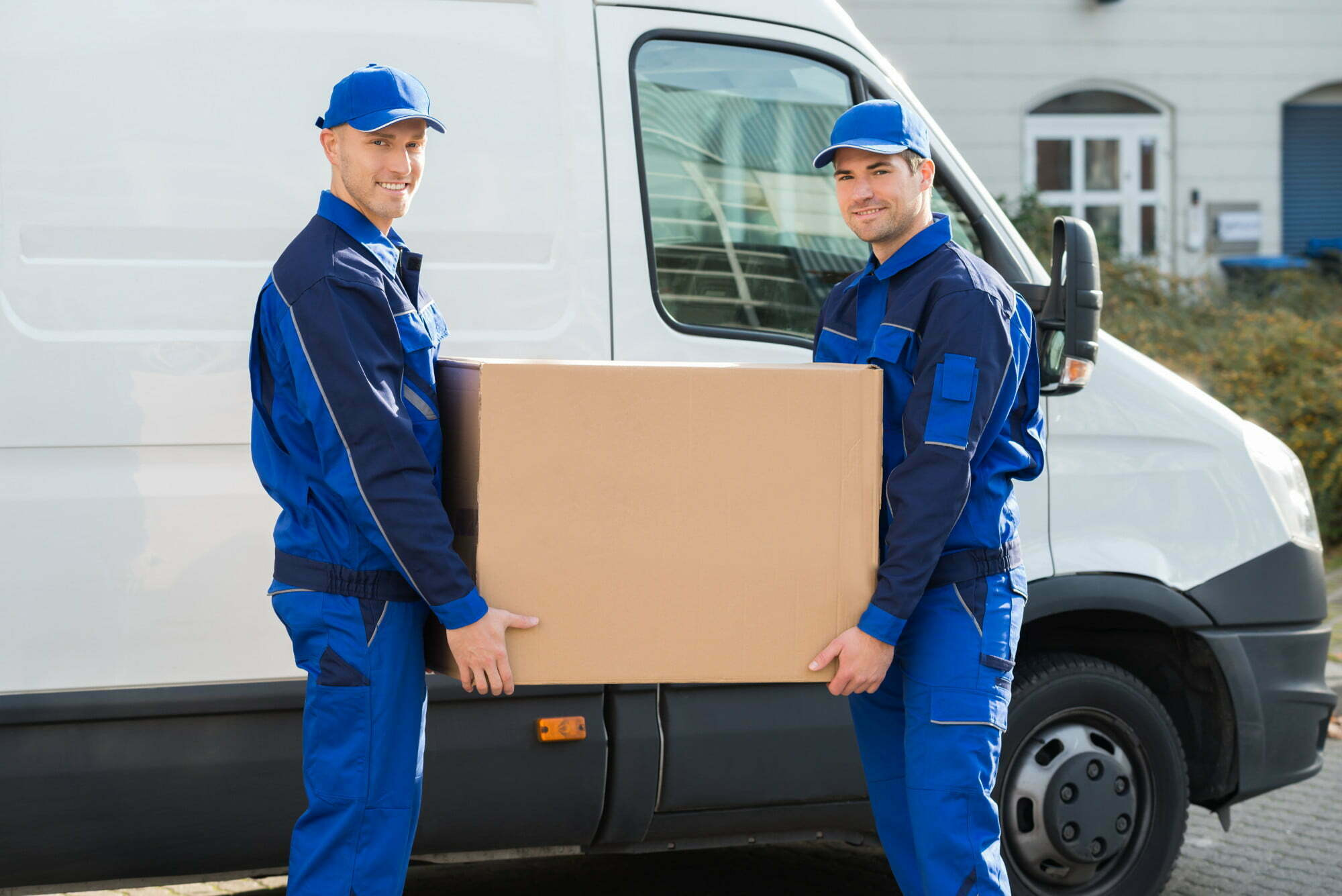 Chicago moving company employees holding a box next to a moving van
